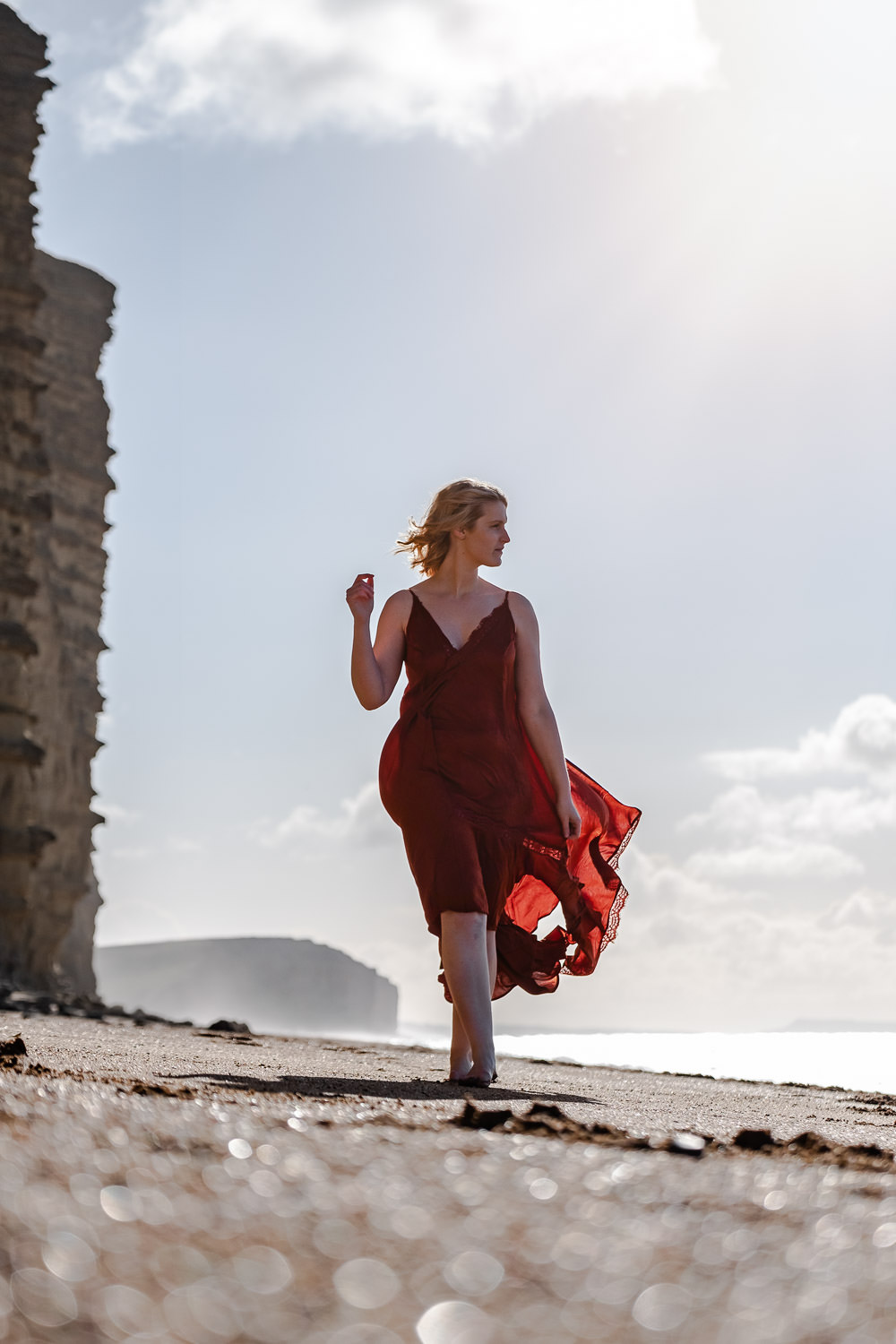 Woman walking along the beach at West Bay, looking out to sea as her skirt flows behind her in the gentle breeze