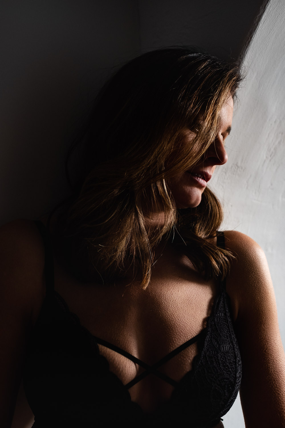Woman leaning against the wall in a black bra as the light falls across one side of her, with the other half in shadows.