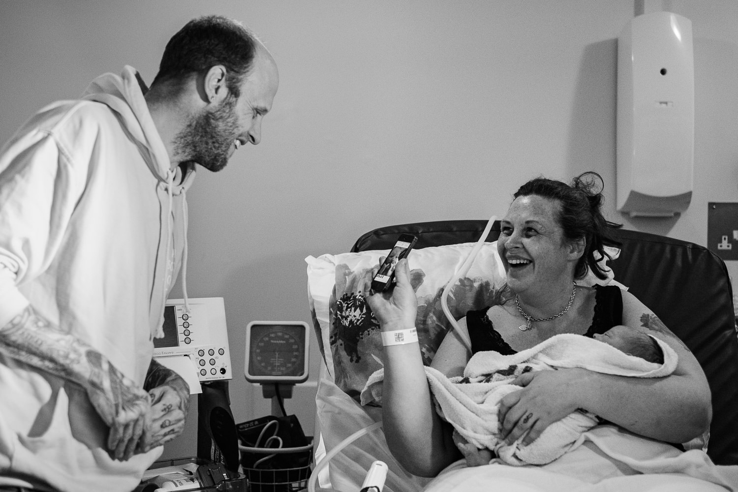 Mother laying in hospital bed, craddling newborn daughter as she shows her partner a picture on the phone.