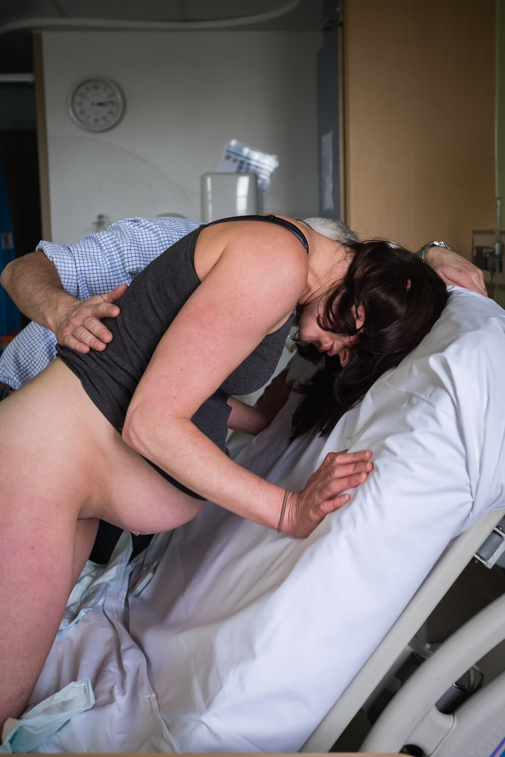Labouring mother on her knees, leaning into the back of the hospital bed as she works through a contraction.