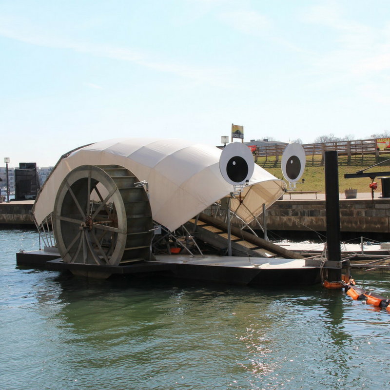 Mr. Trash Wheel - In Baltimore, the Inner Harbor Water Wheel -or Mr. Trash Wheel as residents have lovingly named him -combines old and new technology to harness the power of water and sunlight to collect litter and debris flowing down the Jones Falls River.The river's current provides power to turn the water wheel, which lifts trash and debris from the water and deposits it into a dumpster barge. When there isn't enough water current, a solar panel array provides additional power to keep the machine running. When the dumpster is full, it's towed away by boat, and a new dumpster is put in place. Learn more!