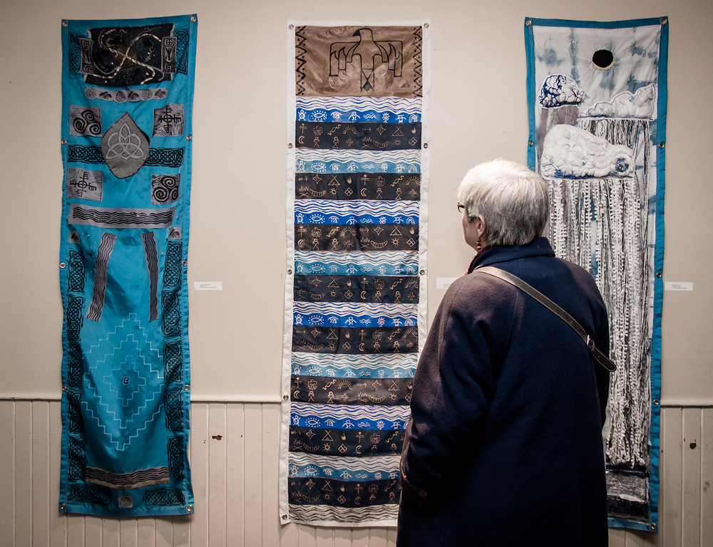 A Water Docs patron engages with several pieces from    Water Advisory!   , on display at the 2018 Water Docs Film Festival.