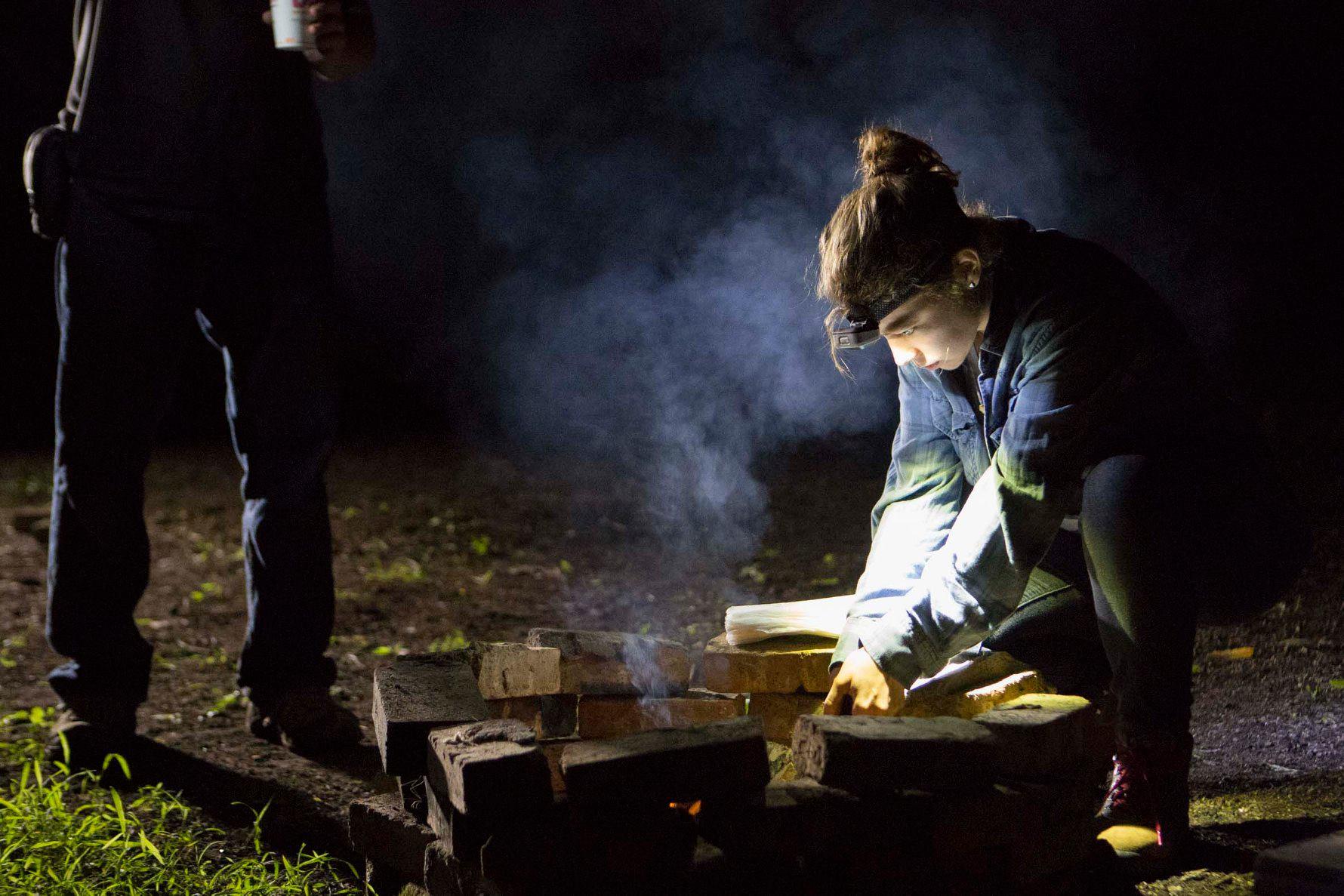 Caitlin Maldonado preps a fire pit on the set of Cellar Door.