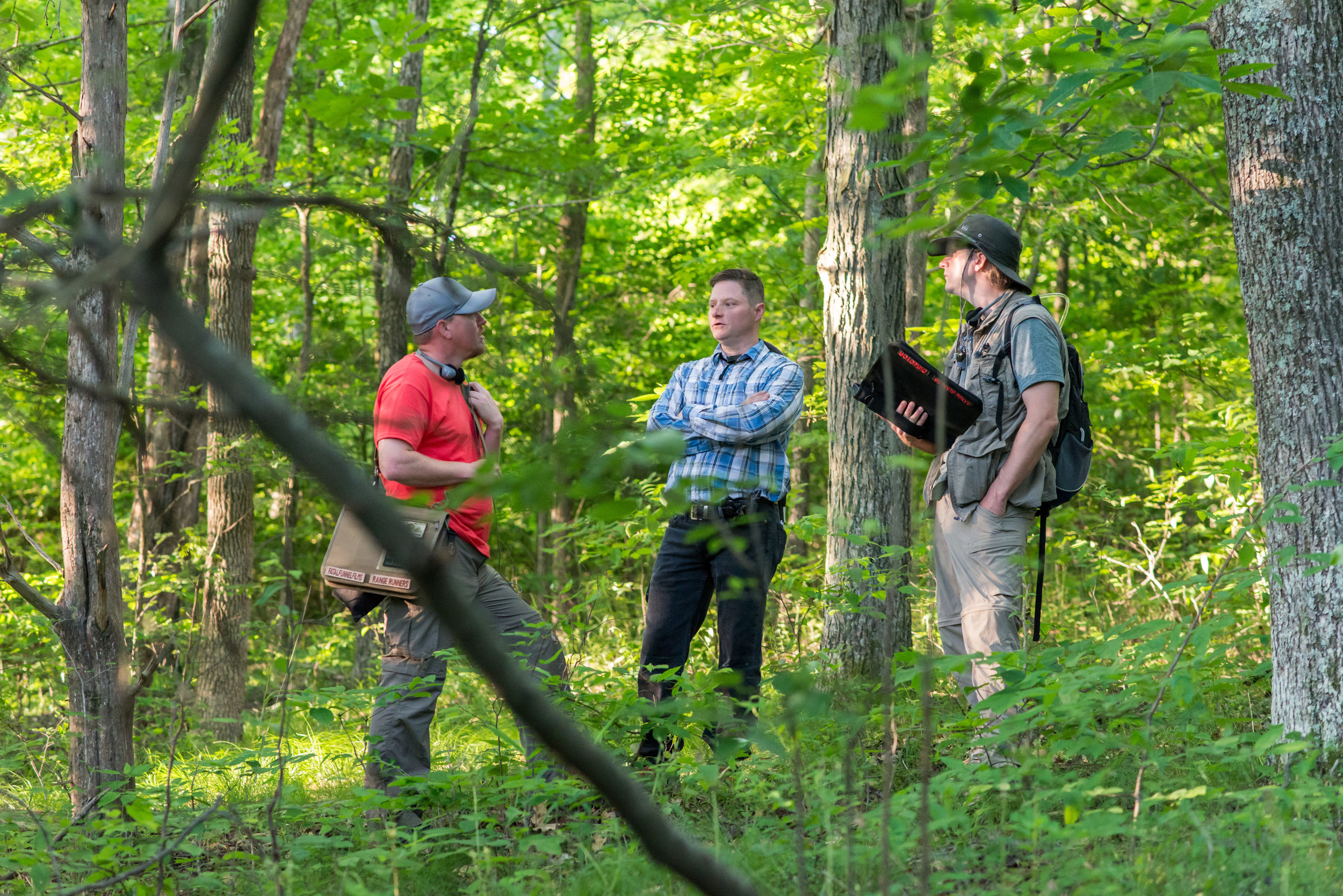 Devon Colwell, Darryl Miller, and Philip S. Plowden discuss a shot in the woods.   Photo credit,  Nathan Fortmeyer