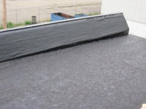 This parapet wall and low slope surface has been primed with an asphalt-based primer prior to the application of Peel & Seal®.