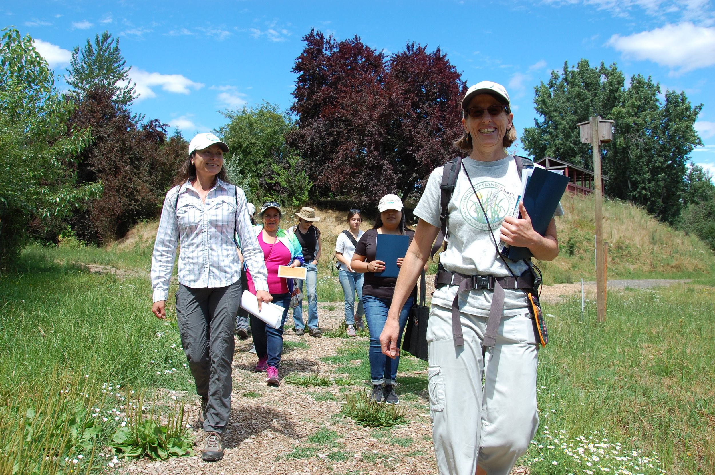 Local ecologists, Lorena (left), and Shari (right), lead members of the group through Jackson Bottom Wetlands. The blue folders contain facts and information that Naturalists will share with their walking groups, both in English and Spanish, as they explore the wetlands.