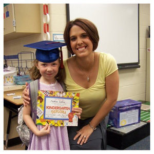 a young girl graduating from elementary school next to her teacher