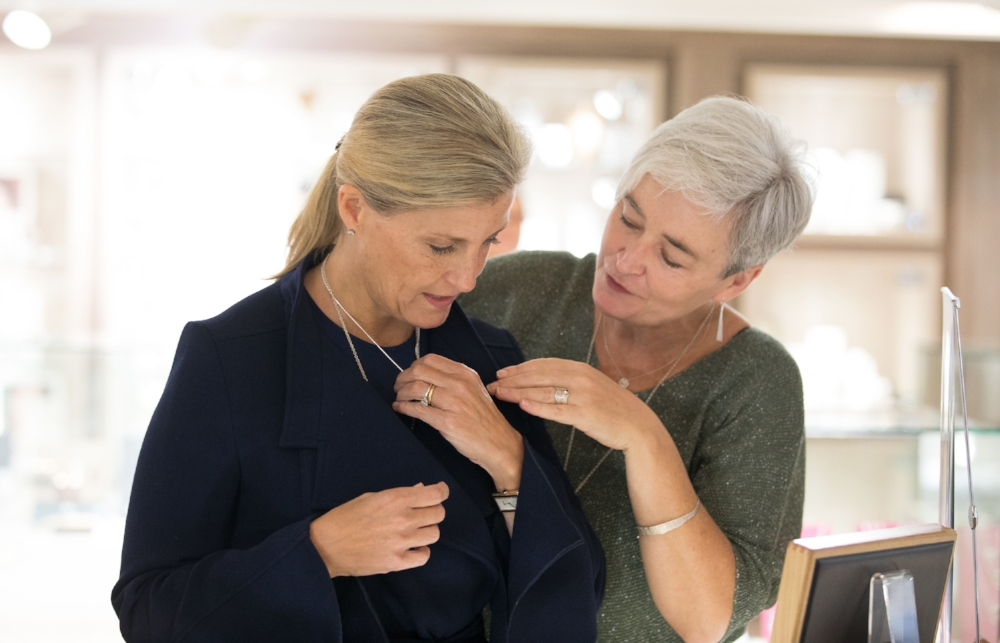 HRH Sophie Countess of Wessex tries on the new Croi Sliogan pendant with assistance from Martina