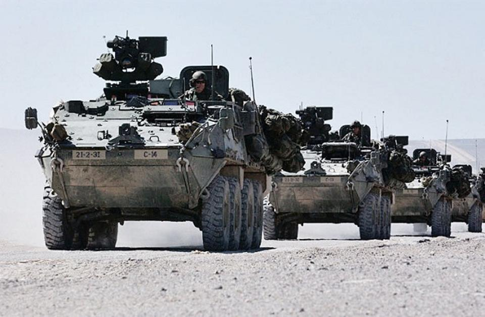 A column of Stryker troop carriers at the Army's national training center. The eight-wheeled Strykers have performed well fighting insurgents, but they need better underside protection and more powerful guns to deter Russian moves in Europe. (Public Domain, Wikimedia Commons)