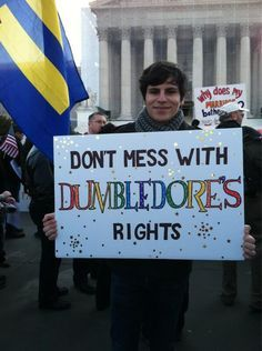 "A man holding a rainbow sign reading ""DON'T MESS WITH DUMBLEDORE'S RIGHTS."" He is at a protest."