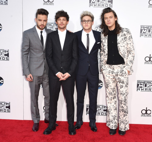 A photograph of Liam Payne, Louis Tomlinson, and Niall Horan all wearing relatively conservative suits. Harry Styles wears a flamboyant floral suit.