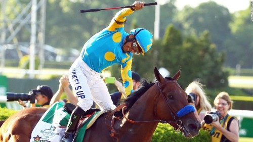 A photograph of a jockey celebrating as he rides the horse American Pharoah.