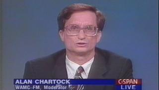 Dr. Alan S. Chartock, a man wearing very 1980s glasses.