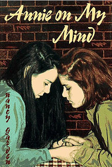 The cover of  Annie On My Mind , by Nancy Garden: two teen girls clasp hands and press their foreheads together.