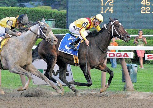 A horse, Rachel Alexandra, mid-race, ridden by a jockey.