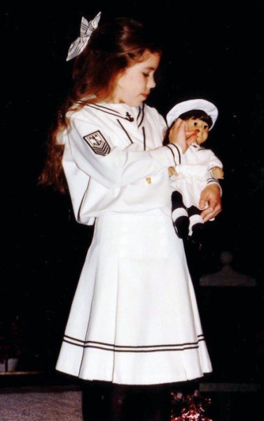 Elizabeth as a child, carrying her Samantha doll. Both are dressed in matching sailor dresses.