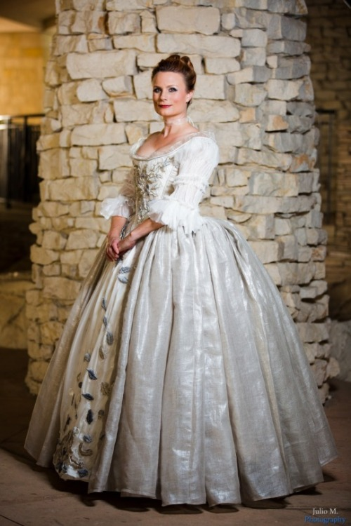 Teresa wearing the wedding dress from  Outlander —a pearl silk gown with embroidered metallic leaves all down the bodice and a very large and sweeping skirt—posing in front of a stone wall.