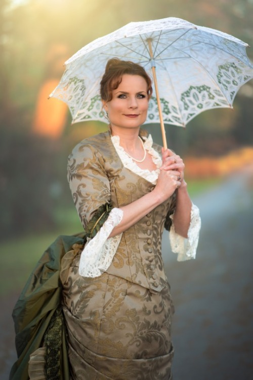 Teresa dressed in a Victorian costume of golden-green brocade, with lace at cuffs and collar, an enormous bustle, and a white lace parasol.