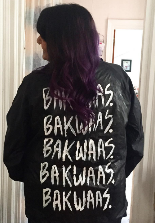 "Preeti wears a black jacket with ""BAKWAAS."" painted five times in white on the back."