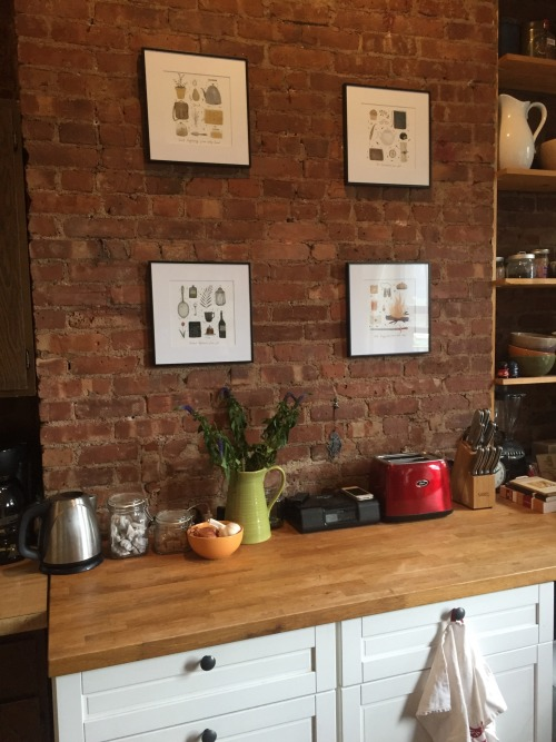 A brick kitchen wall with four framed and hung pieces of art on it, each featuring items that represent one of the four Hogwarts houses.