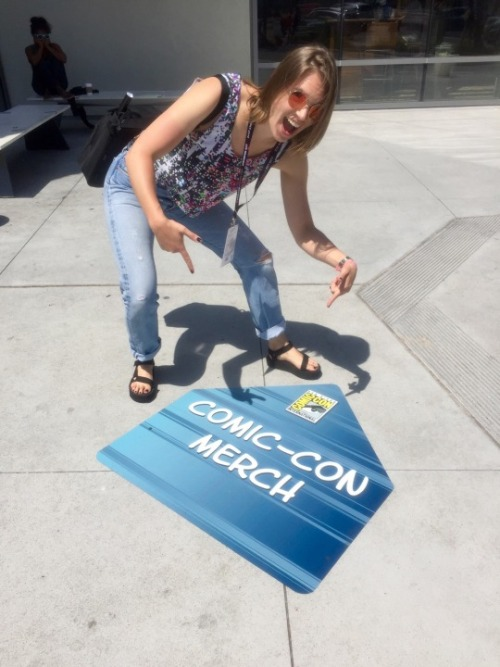 Flourish stands outside the San Diego Convention Center and points at a sign on the asphalt reading COMIC-CON MERCH.