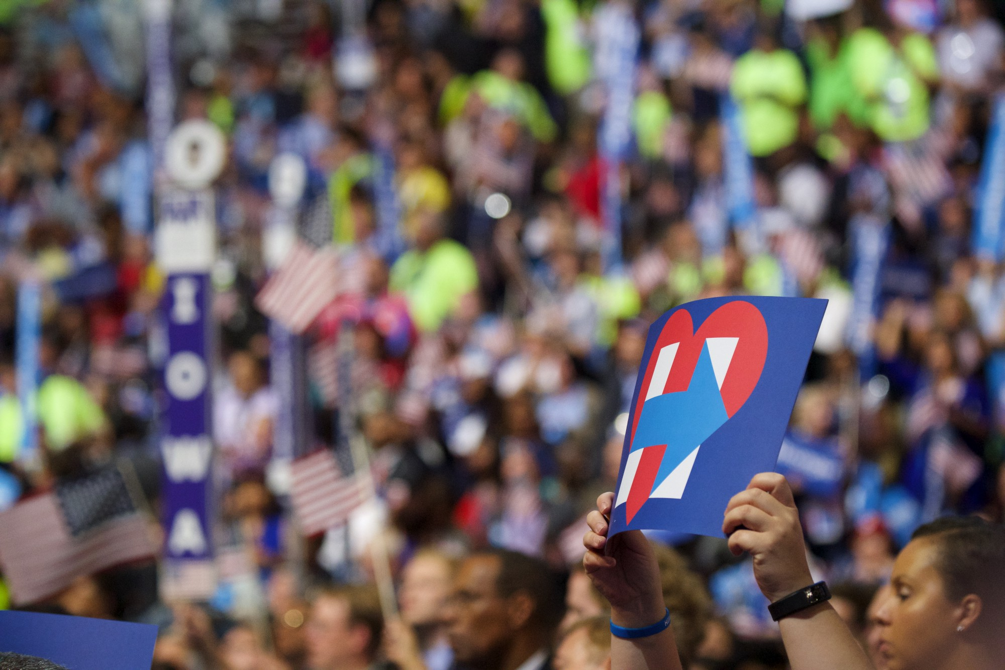People at a rally hold up Hillary signs.  Image credit:  Gregory Reed/Shutterstock