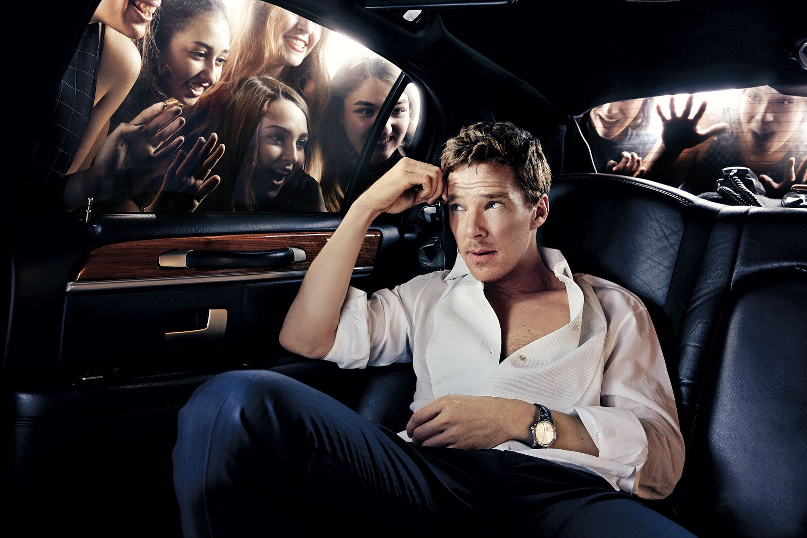Benedict Cumberbatch in a limo with girls pressing on the windows staring at him.