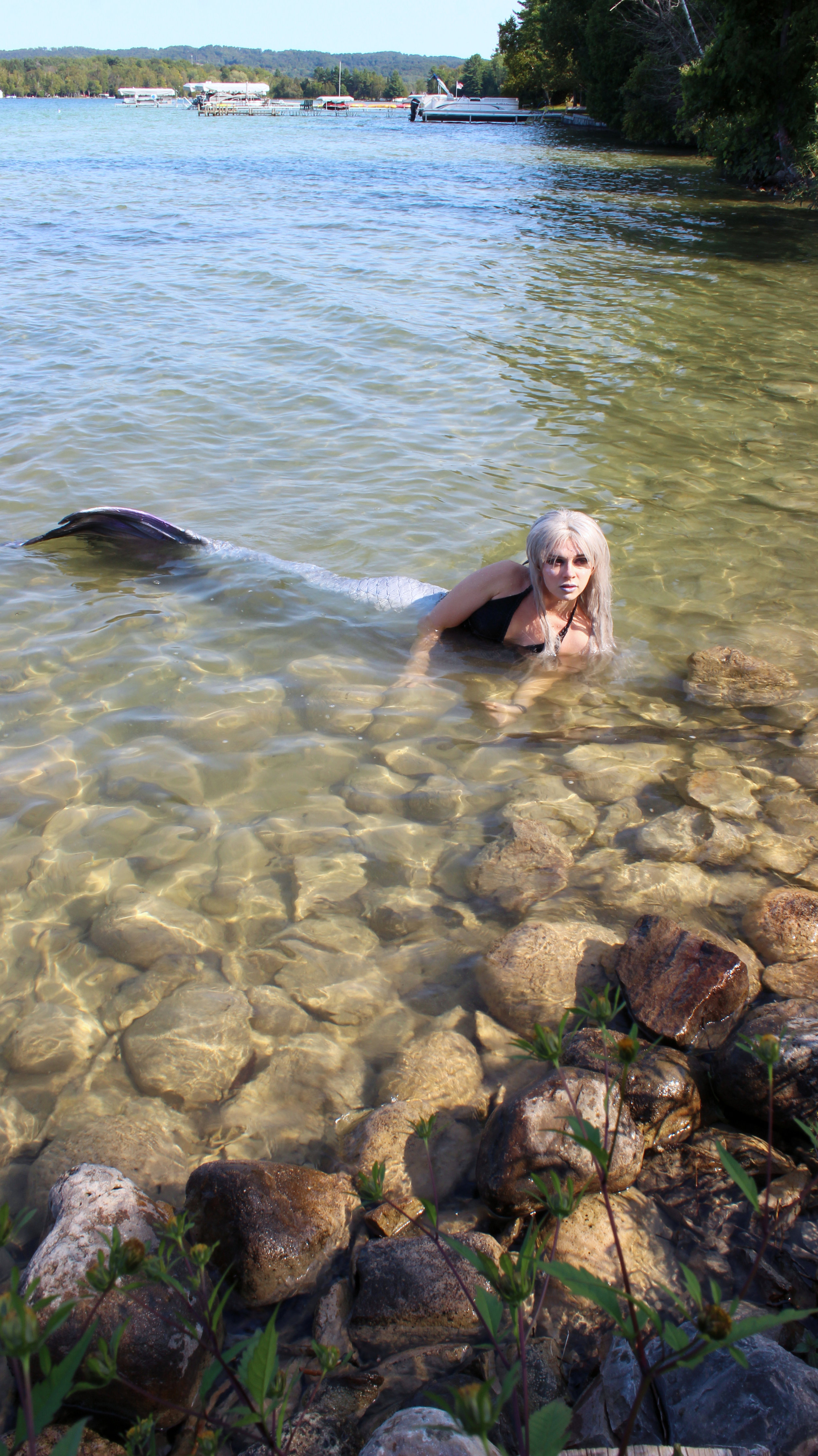 A photograph of a real mermaid. Mermaid Phantom, a professional mermaid cosplayer, is posing near the shore in a small Michigan lake.