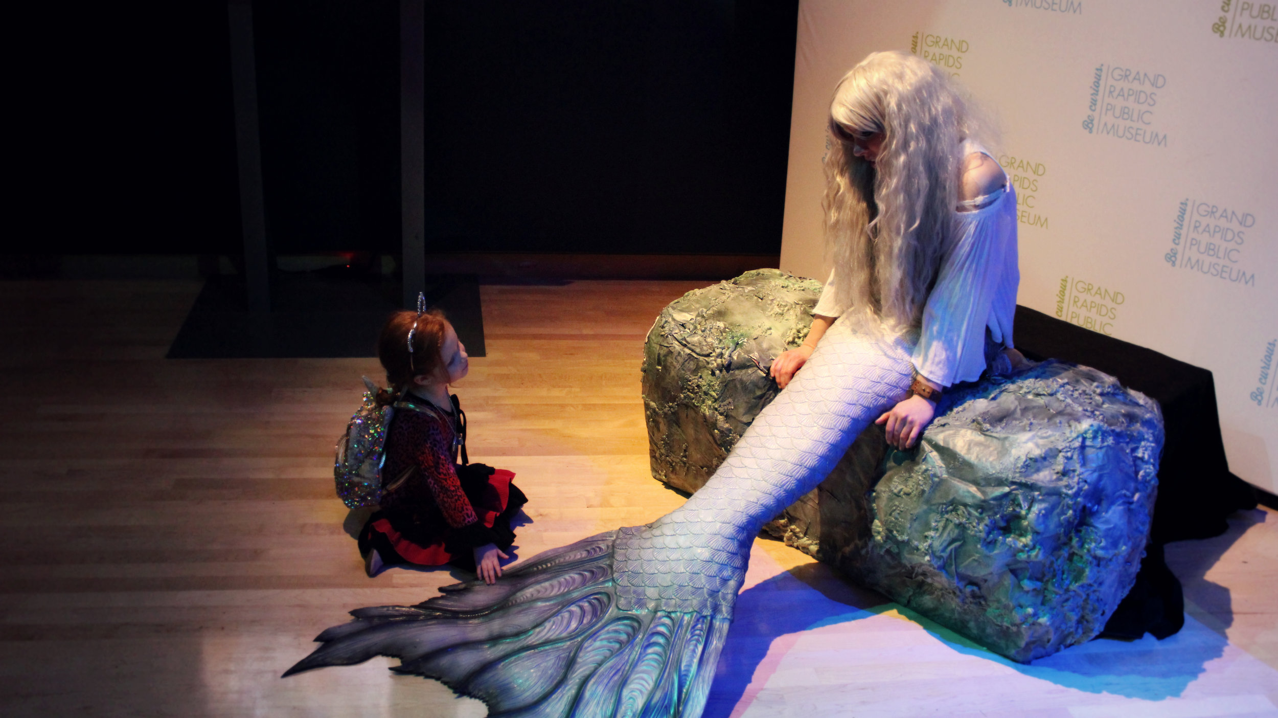 "Live Mermaid at the Grand Rapids Public Museum for the ""Dragons, Unicorns & Mermaids"" exhibit. Guests at the museum were allowed to take pictures with a real mermaid, ask her questions and touch her mermaid tail! Hire Mermaid Phantom, a professional mermaid, for your next big event today!"
