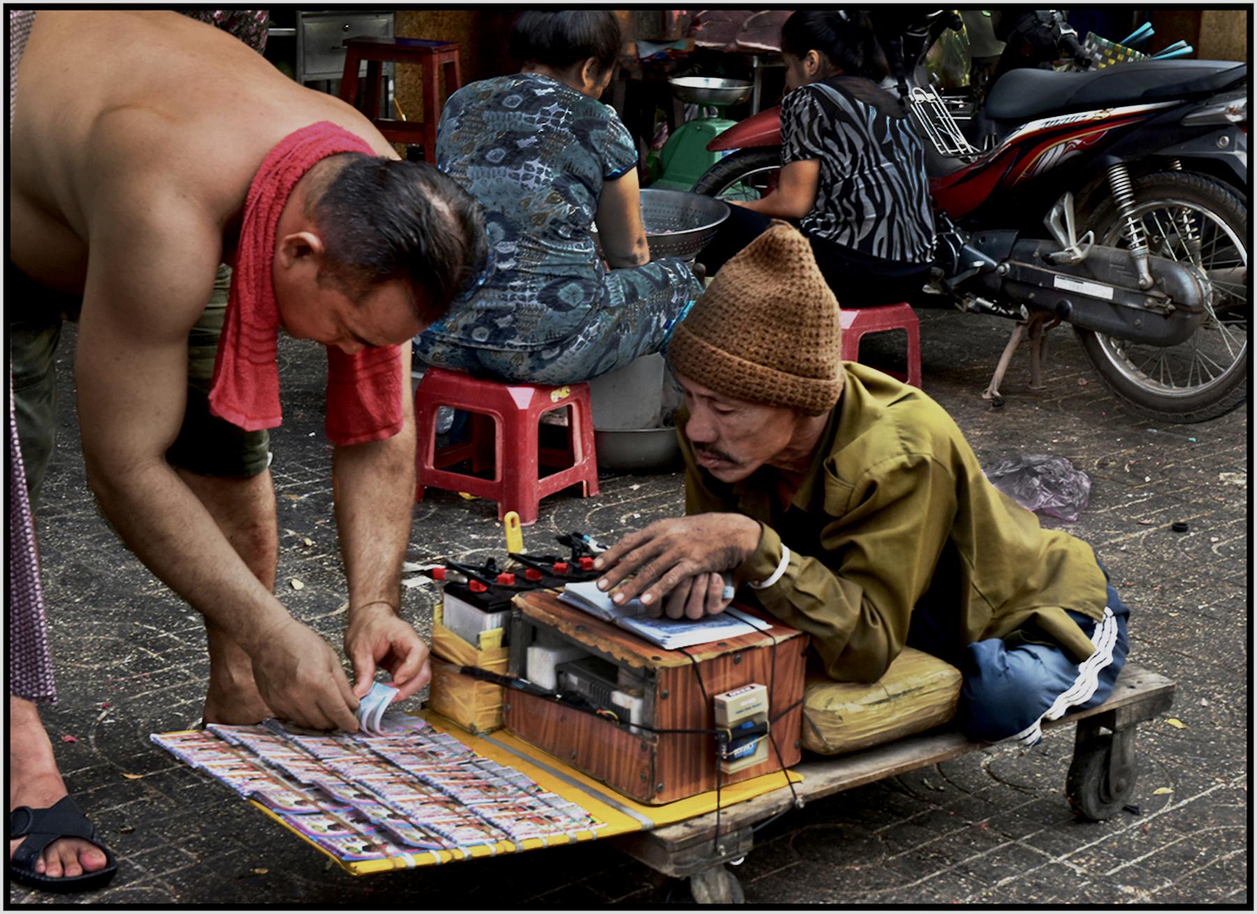 Man with no legs sells lottery tickets amidst vendors at the Binh Tay Market, Cholon, Saigon/HCMC, Dec. 2015. #3848