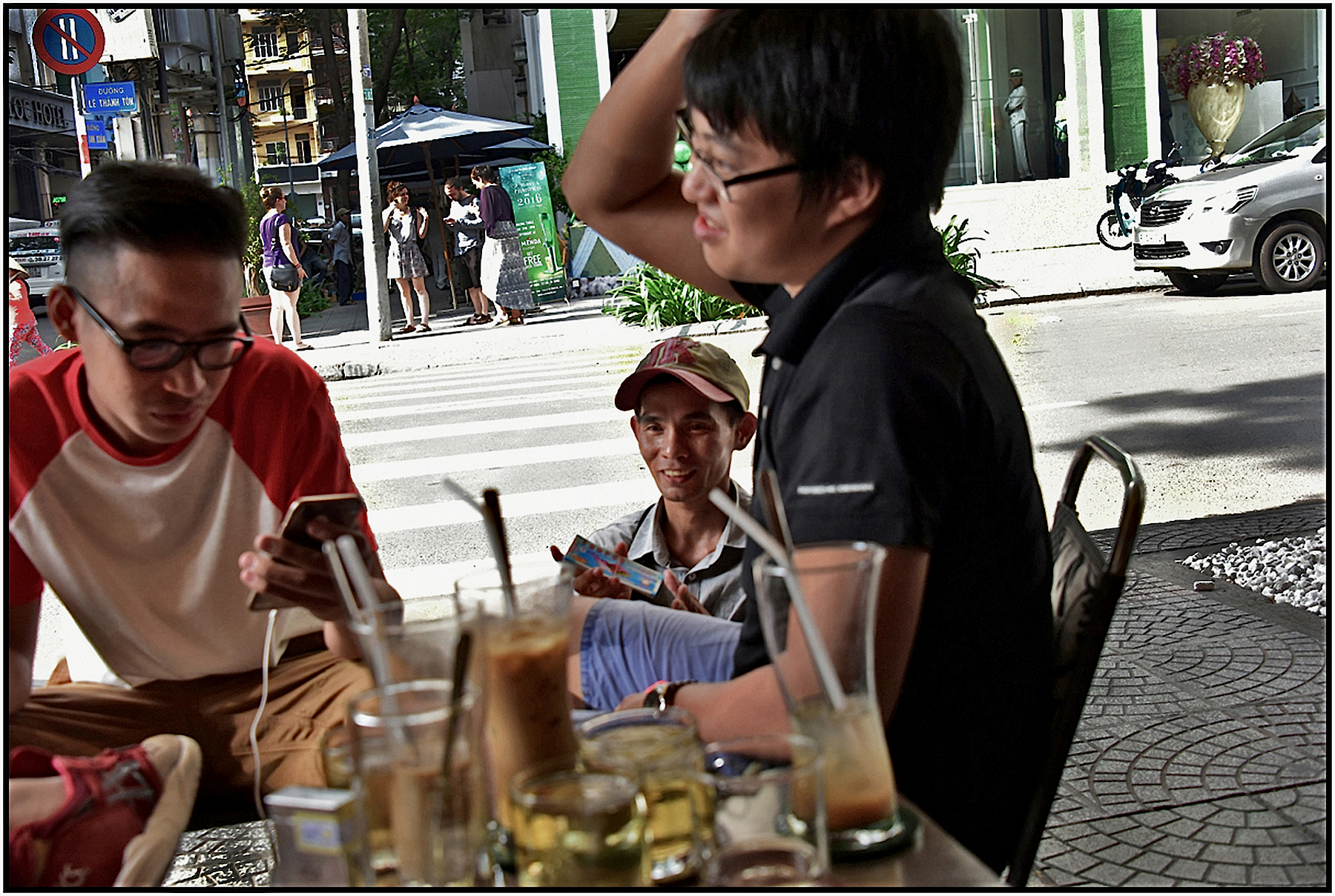 Four teenage boys at a Coffee Cafe as a legless man attempts to sell lottery tickets. Saigon/HCMC, Jan. 2016. #0155