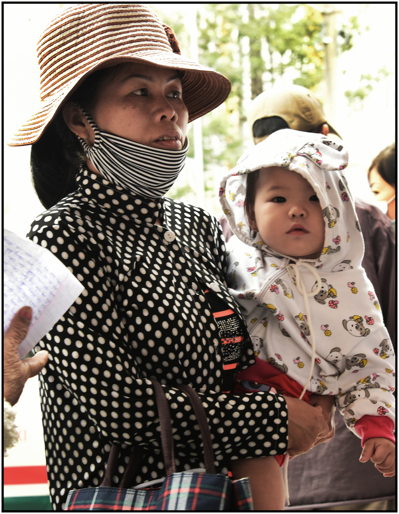Woman with child wait outside Binh Tay Market, for merchendise she purchased, to be delivered to her vehicle, Binh Tay Market, Cholon, Saigon/HCMC, Dec. 2015