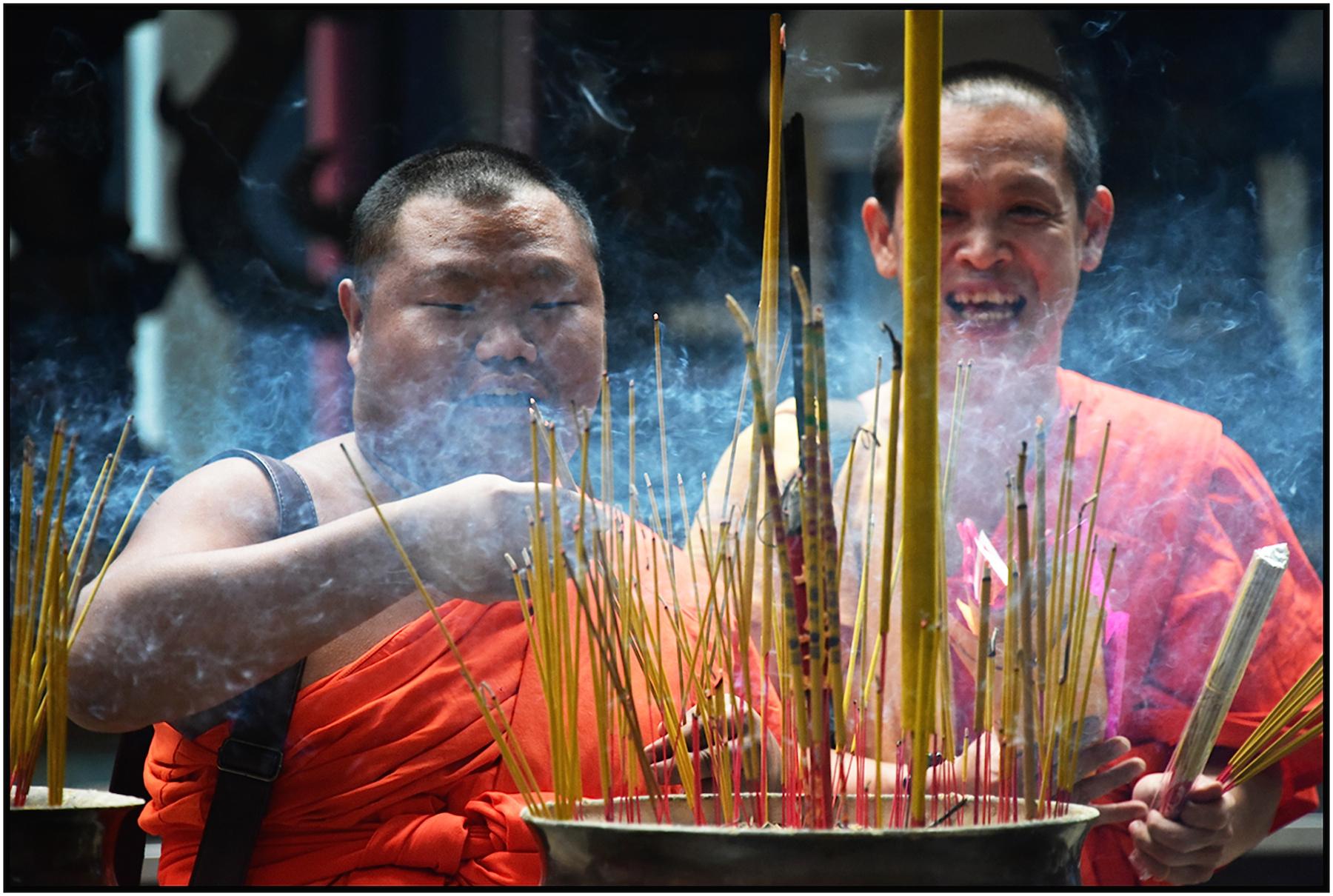 Monk burns his finger, his colleague laughs, ———Pagoda, Saigon/HCMC, Dec. 2016. #4342