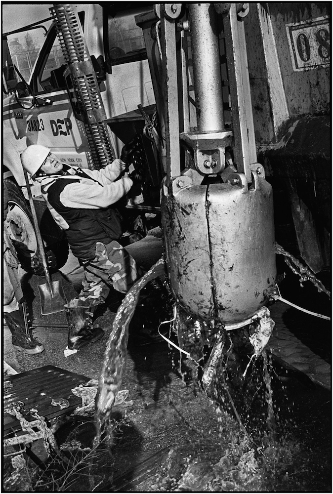 Marga Rodriguez, a Department of Environmental Protection Laborer, operates a sewer basin cleaning machine, after a devastating 30-inch water main break in Carroll Gardens, Brooklyn. 1994.