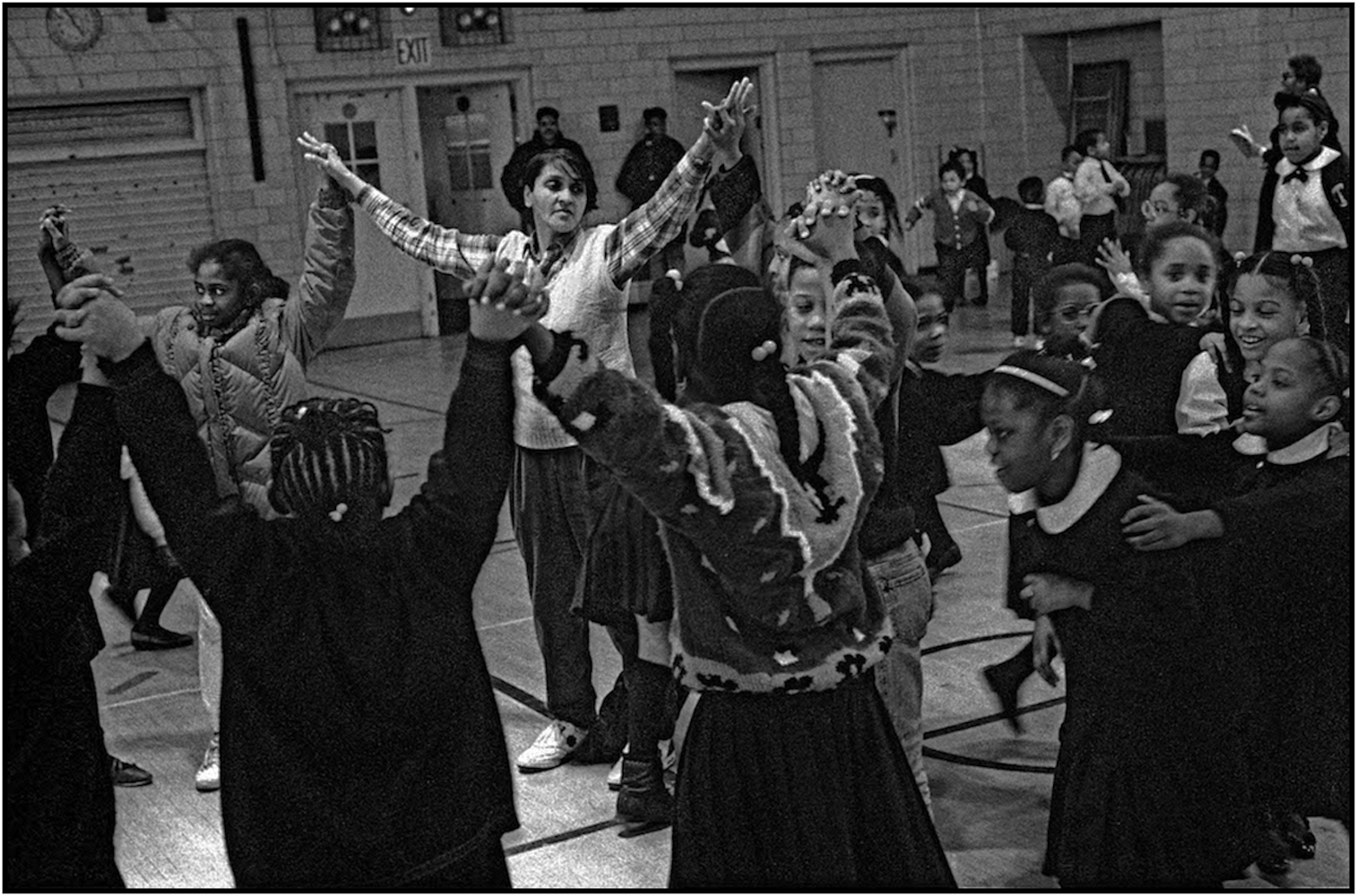 School Aide Gloria Jackson leads children at circle game in an after-school program at P.S. 176, Queens. 1991.
