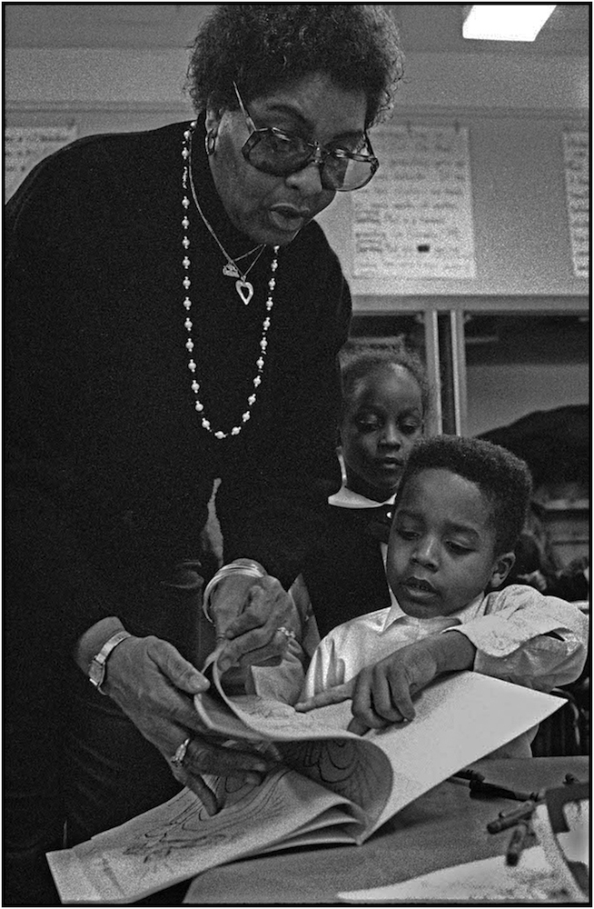 """Francis Bartlett, a NYC Board of Education Family Worker, helps a student in an after-school """"latch key program,"""" P.S. 176, Queens. 1991."""
