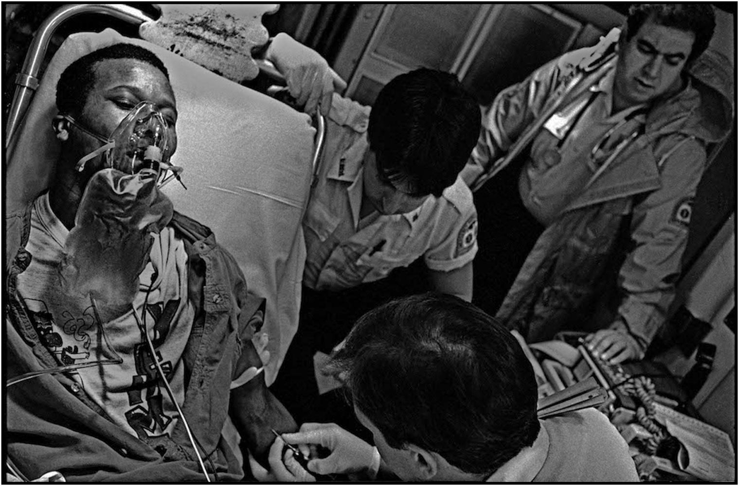 EMS paramedics and technicians, Howard Spielman, Michael Ralmer, and Myra Torres,treat a crack overdose patient. 1991.