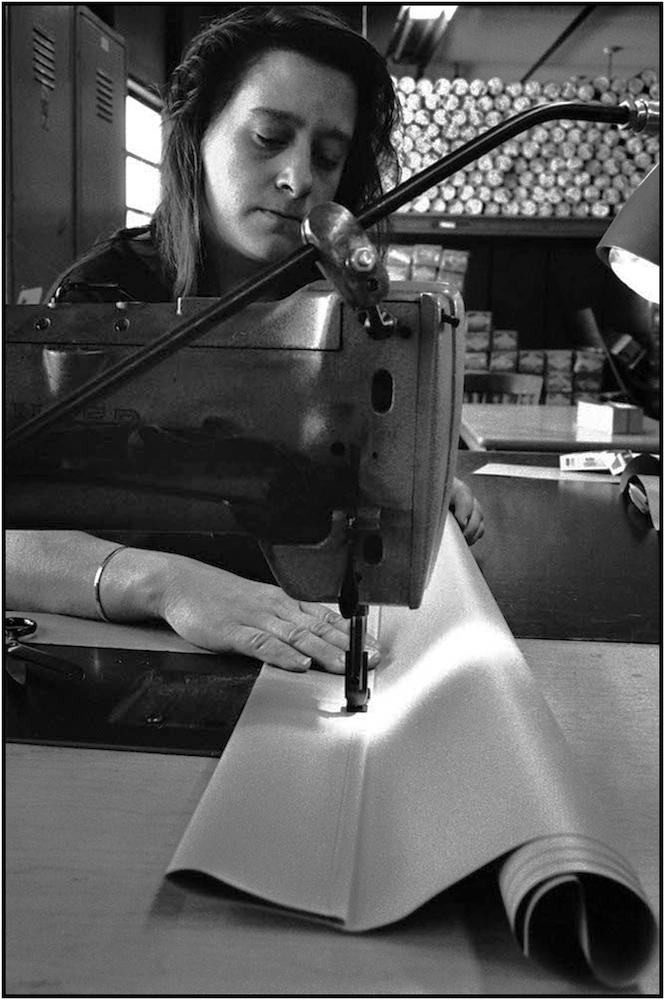 Worker manufactures school window shades .  19--.