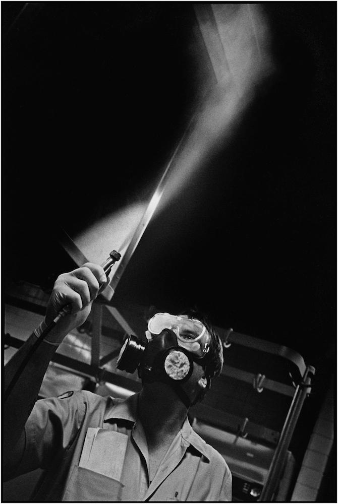 Pest control technician Malcolm Adams fogs an elementary school kitchen in Brooklyn. 1993.