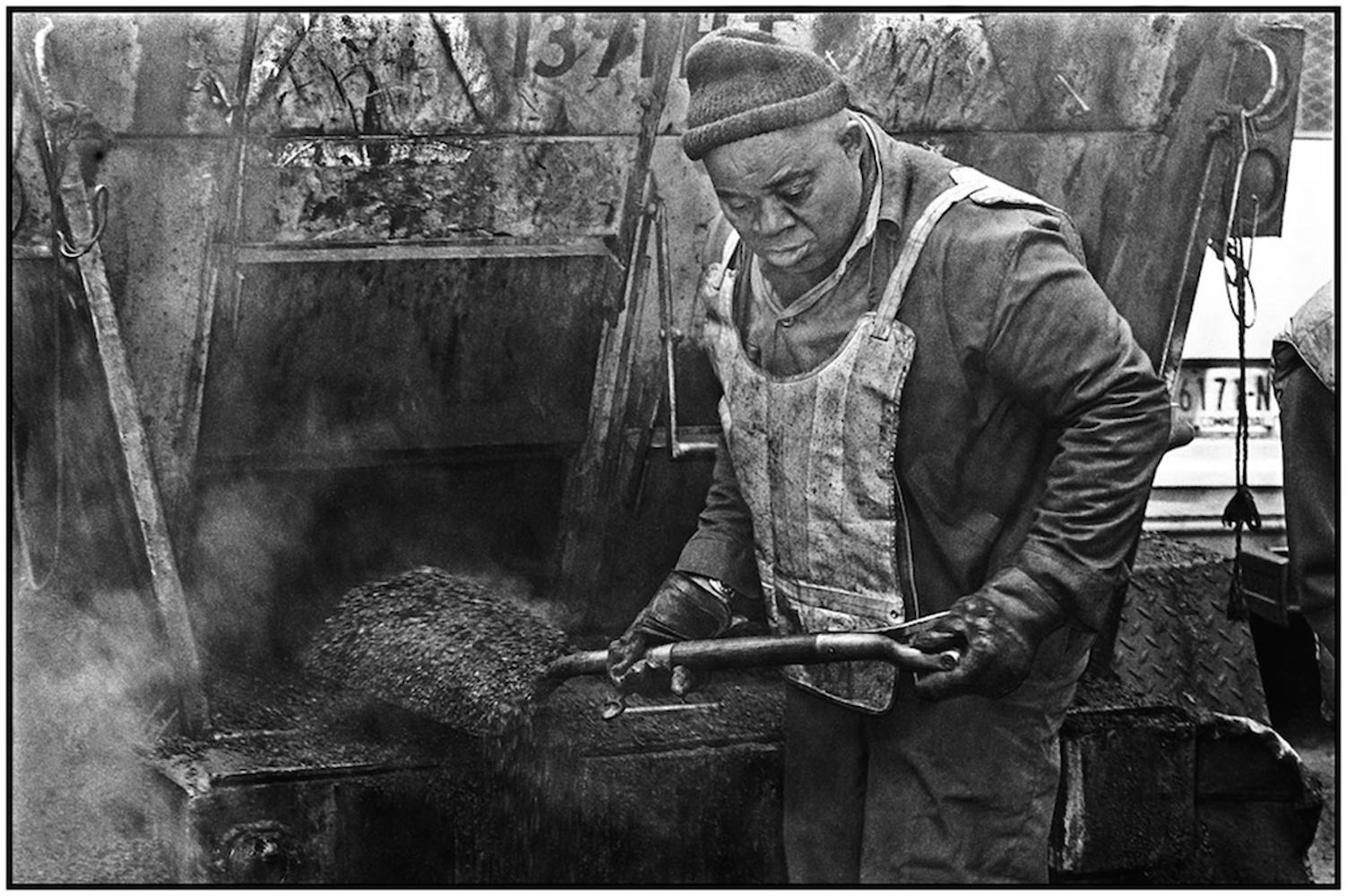 Highway Repairer Chester Bailey shovels hot asphalt to fill pothole in midtown Manhattan. 1984.