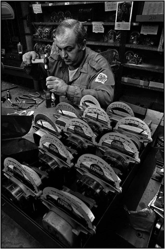 Worker repaires parking meters, Maspeth Queens shop.