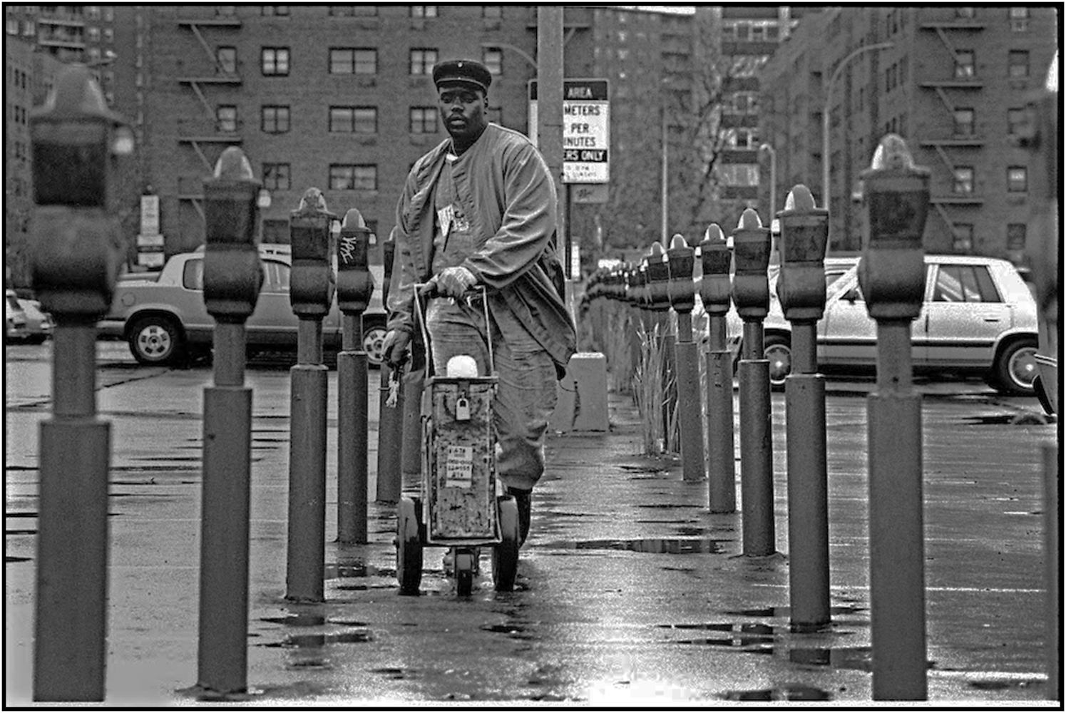 Keith Rhem, a parking meter service worker, collects quarters in a Queens municipal parking lot. 1990.