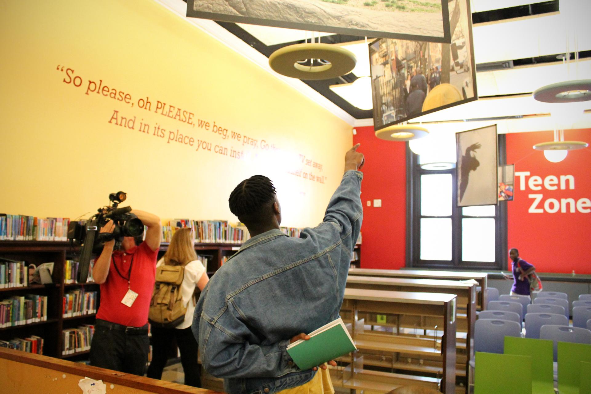 Prince explaining his work to New York One news cameras.