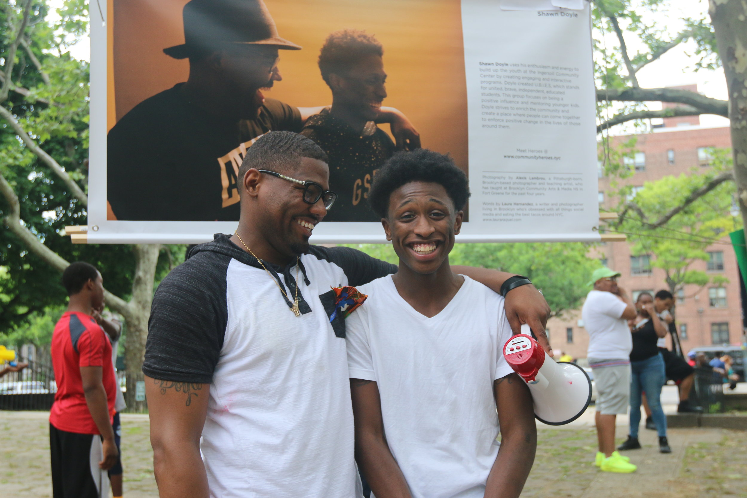 Shawn Doyle (left) and D'Angelo Rembert AKA Dee Dee (right) stand in front of their banner at the annual FSR Peace Fest in Fort Greene, Brooklyn.