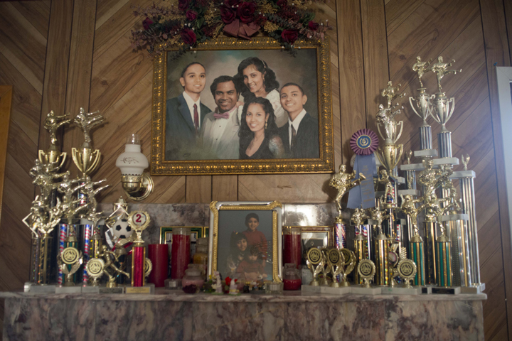 A family portrait of the Bujan family hangs above the mantle in Ms. Bujan's parents house in Queens, NY.  The mantle is covered with martial arts trophies Ms. Bujan and her two brothers have won over the years.