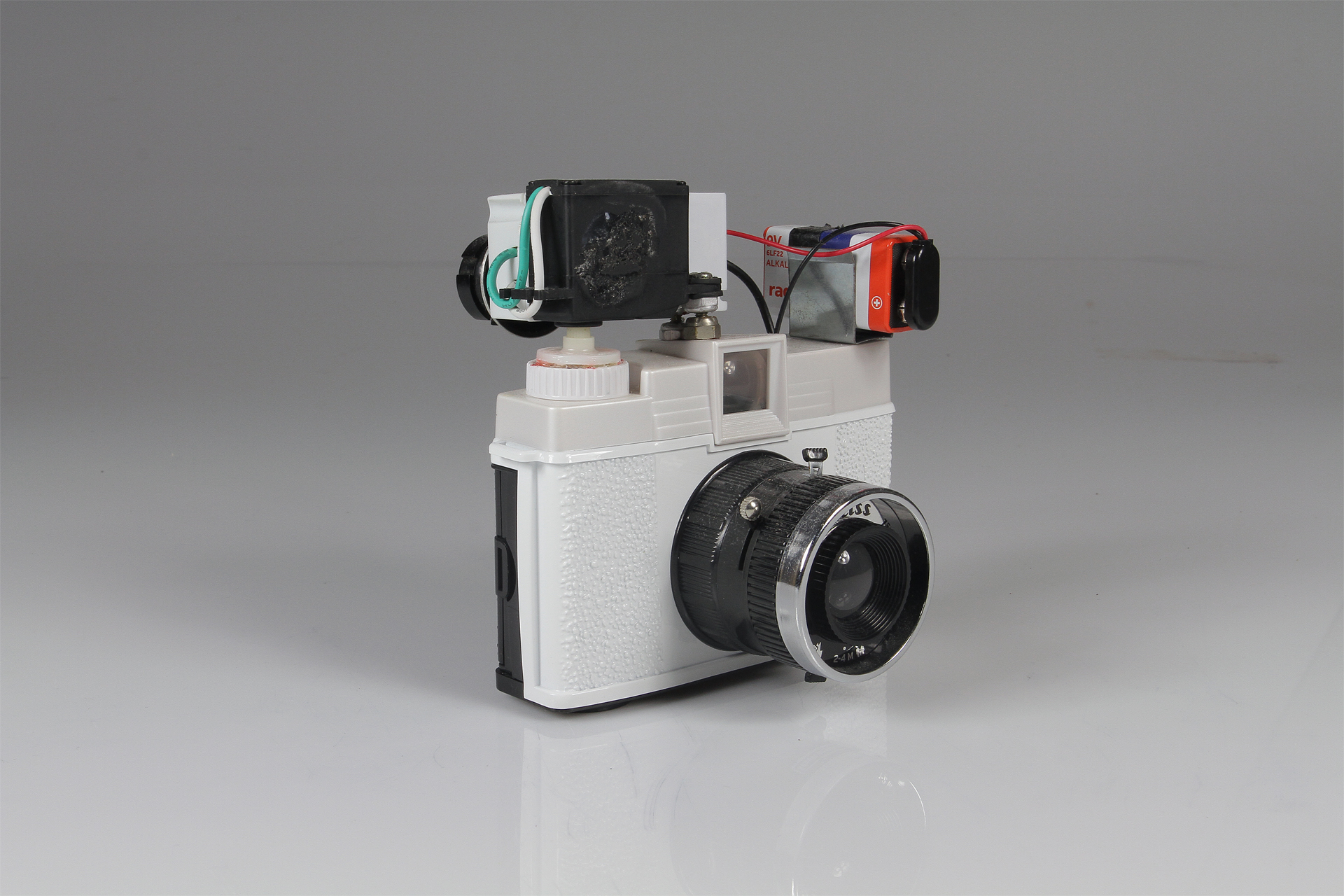 Diana Slitscan Camera  2016.  Modified Diana+ with 35mm film back for Strip Photography.  Diana+ camera, modified servo motor, pulse-width modulation circuit (for motor speed control), 9v battery, battery clip, electrical wire, salvaged nuts and bolts.