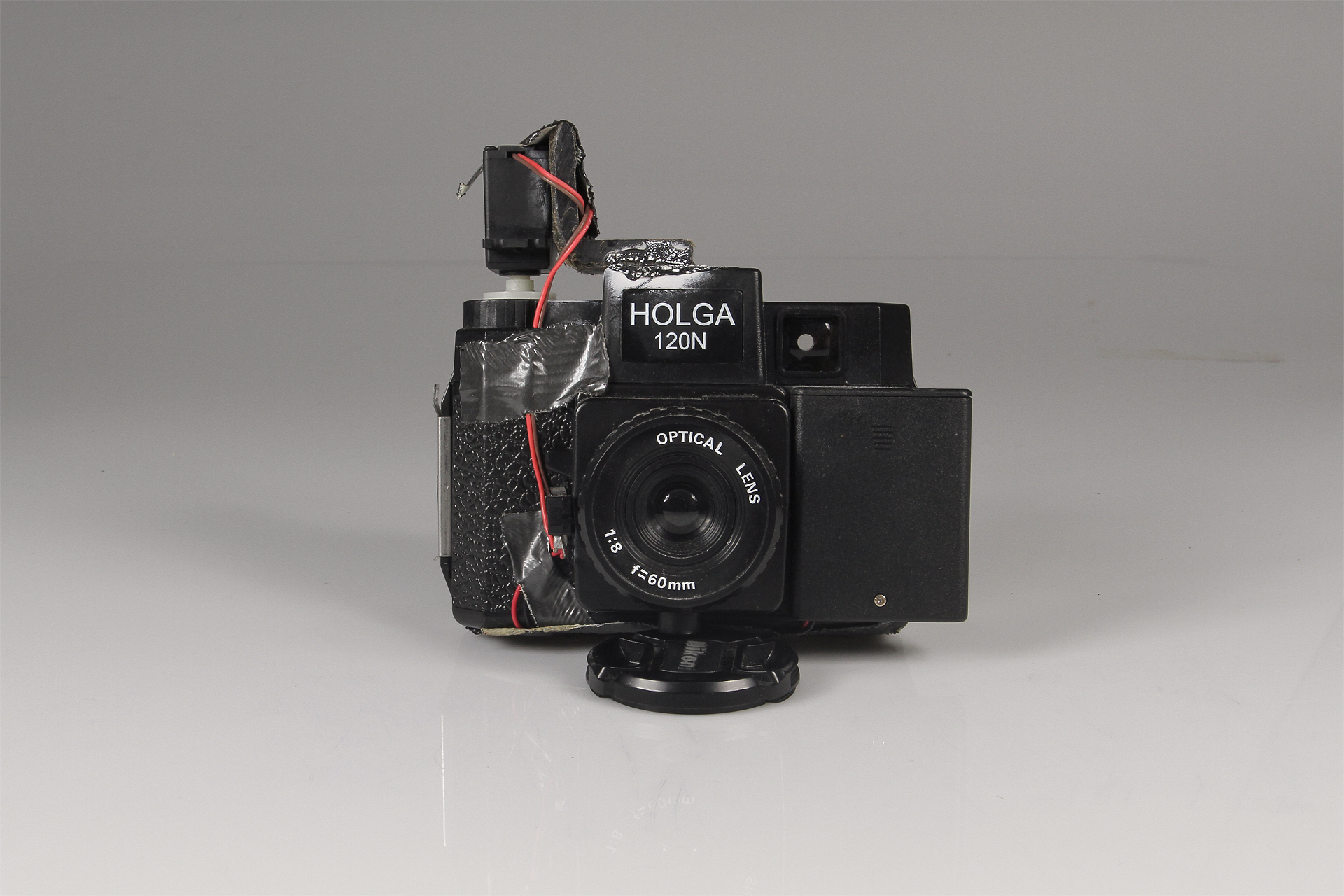 Holga Slitscan Camera  2013.  Modified Holga for Strip Photography.  Holga camera, modified servo motor, 3xAAA battery pack, SPST switch, plastic L bracket, black-rubberized 4x5 film (to make the slit in the camera), electrical wire, duct tape, super glue.