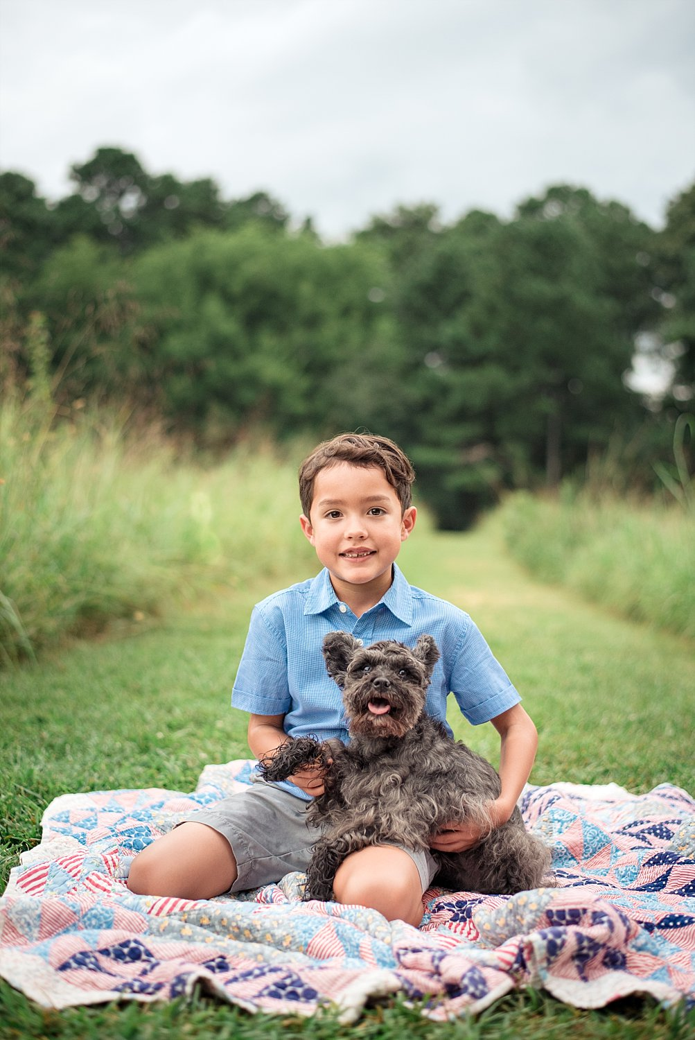 boy and schnauzer sitting on blanket