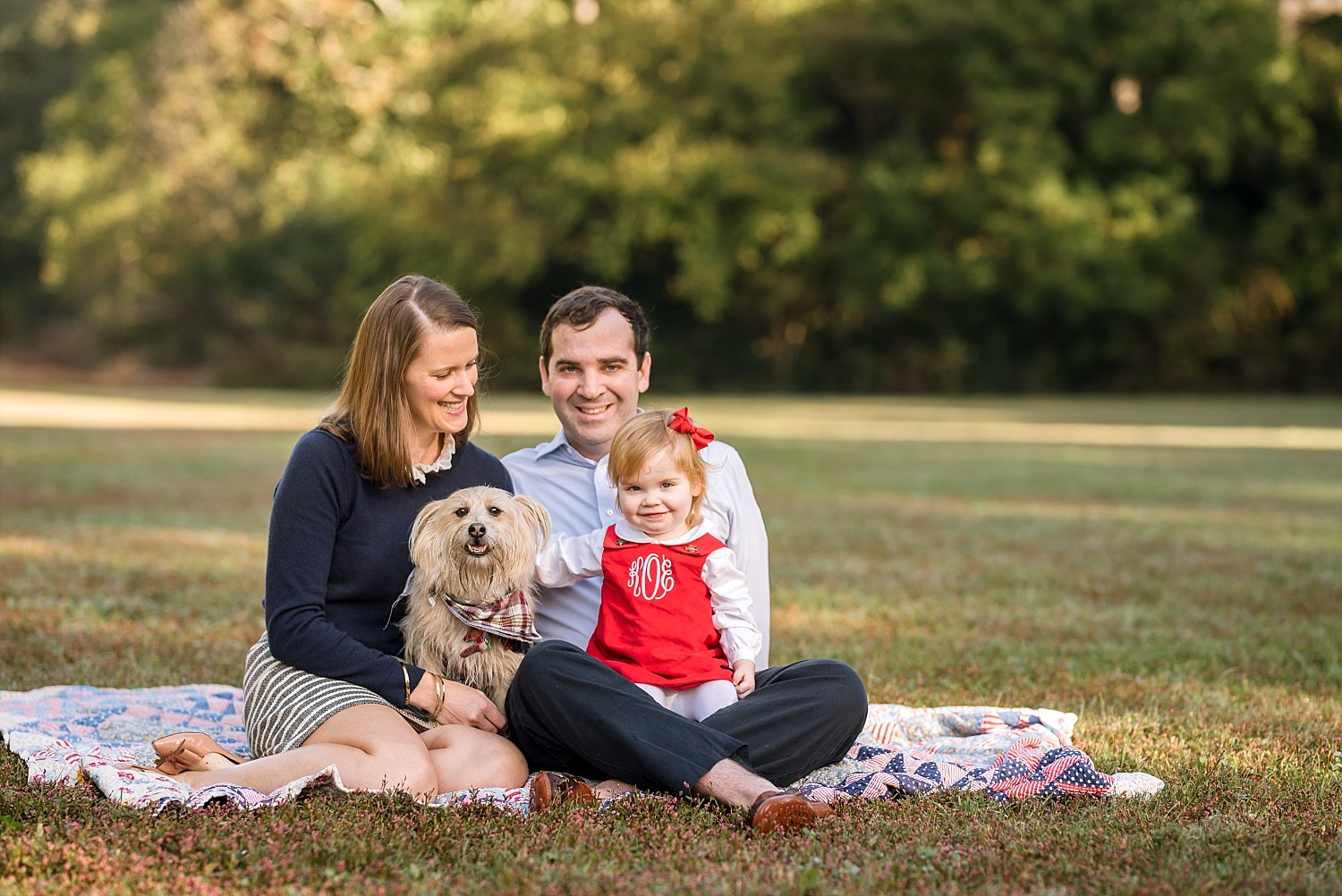 Family of 3 with dog on blanket in park