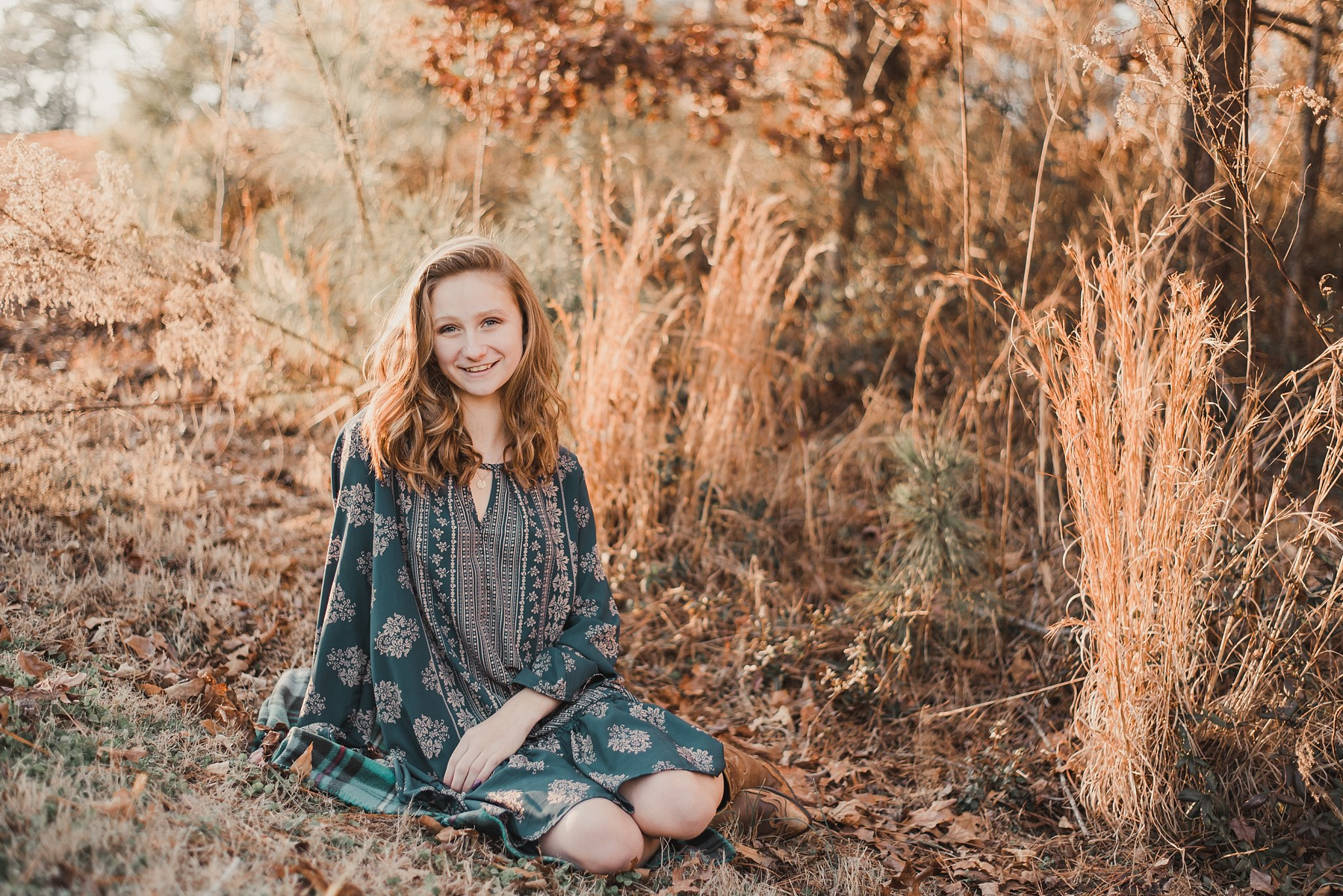 senior girl sitting in tall grass at golden hour